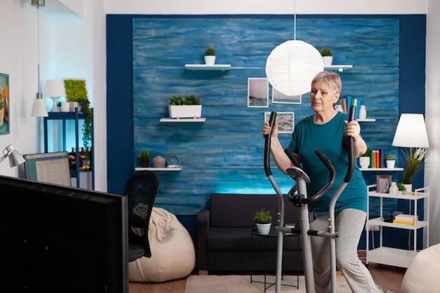 Mulher sênior focada trabalhando na resistência muscular das pernas, ciclismo máquina de bicicleta na sala de estar durante um treino saudável de aeróbica