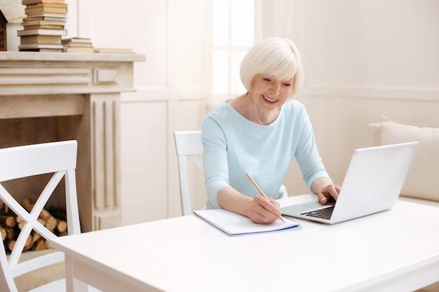Mulher sênior inteligente e elegante usando seu laptop para ler artigos e consultar alguns especialistas interessantes
