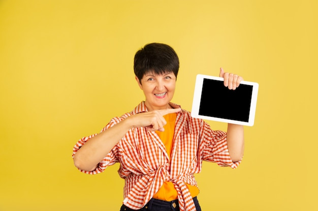 Mulher sênior isolada em fundo amarelo. conceito de estilo de vida de idoso alegre e tecnológico