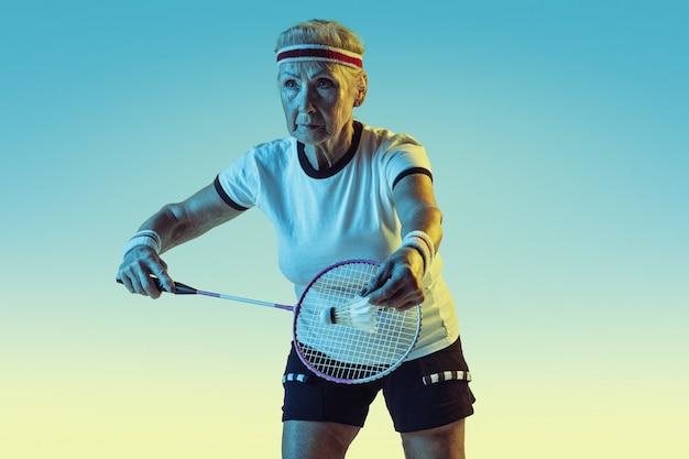 Mulher sênior jogando badminton em roupas esportivas na parede gradiente com luz de néon
