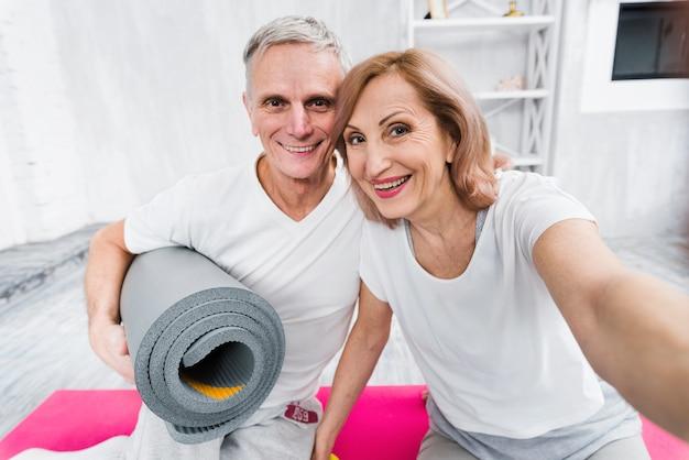 Mulher sênior, levando, selfie, com, dela, marido, segurando, rolado, esteira yoga, casa