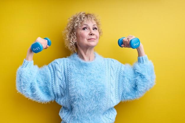 Mulher sênior, levantando halteres isolados, tendo braços musculosos, blusa azul, com cabelos grisalhos.