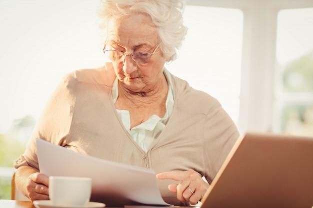 Mulher sênior, lidar com documentos enquanto estiver usando o laptop em casa