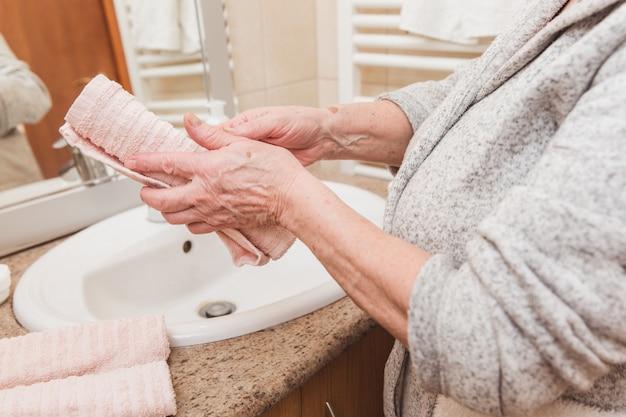 Mulher sênior, limpa, dela, mãos, com, um, toalha, em, banheiro, em, manhã, tempo