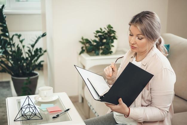 Mulher sênior loira caucasiana trabalhando com alguns documentos de casa