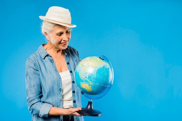 Mulher sênior moderna com globo