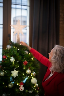 Mulher sênior, montando, árvore natal