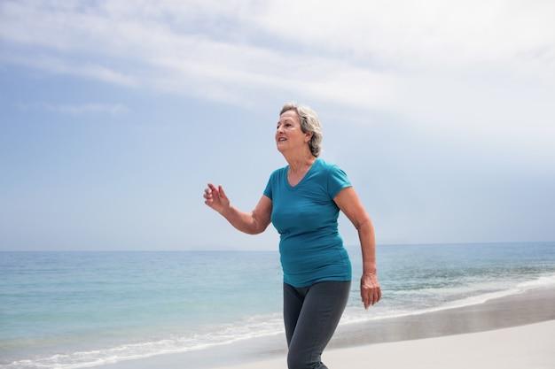 Mulher sênior, movimentando-se na praia