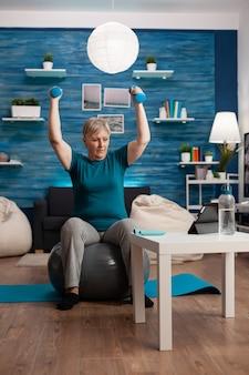 Mulher sênior na aposentadoria, levantando as mãos, fazendo exercícios de braços, usando halteres, sentado em um treino de fitball.