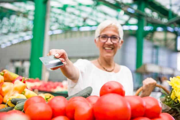 Mulher sênior no mercado verde