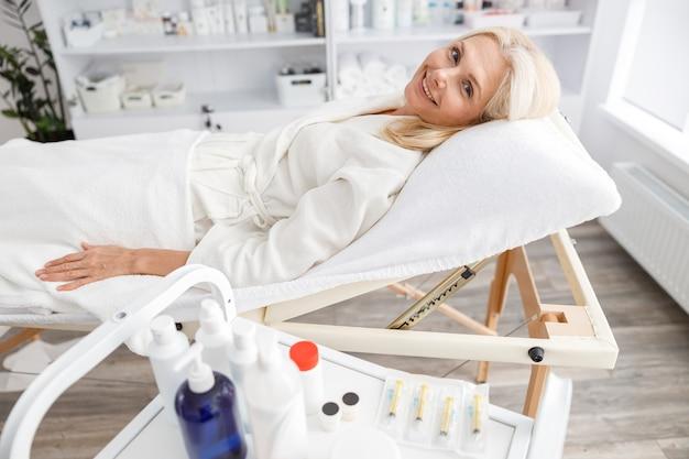 Mulher sênior no ônibus à espera de procedimento cosmético na clínica de cosmetologia estética.
