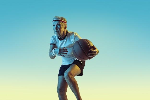 Mulher sênior no sportwear jogando basquete em fundo gradiente, luz de néon. modelo feminino em ótima forma permanece ativo. conceito de esporte, atividade, movimento, bem-estar, confiança. copyspace.