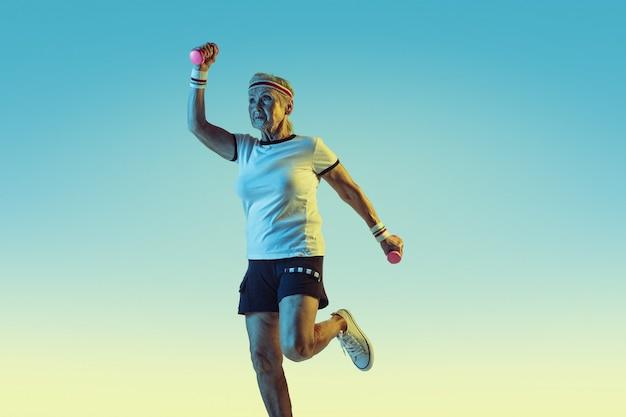 Mulher sênior no treinamento de sportwear com pesos em fundo gradiente, luz de néon. modelo feminino em ótima forma permanece ativo. conceito de esporte, atividade, movimento, bem-estar, confiança. copyspace.