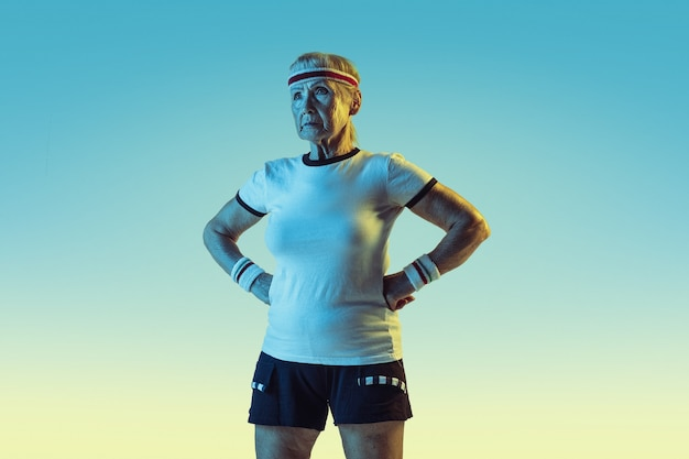 Mulher sênior no treinamento de sportwear e posando em fundo gradiente, luz de néon. modelo feminino em ótima forma permanece ativo. conceito de esporte, atividade, movimento, bem-estar, confiança. copyspace.