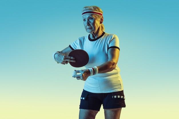 Mulher sênior no treinamento de sportwear em tênis de mesa em fundo gradiente, luz de néon. modelo feminino em ótima forma permanece ativo. conceito de esporte, atividade, movimento, bem-estar, confiança. copyspace.