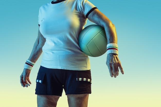 Mulher sênior no treinamento de sportwear no voleibol em fundo gradiente, luz de néon. modelo feminino em ótima forma permanece ativo. conceito de esporte, atividade, movimento, bem-estar, confiança. copyspace.