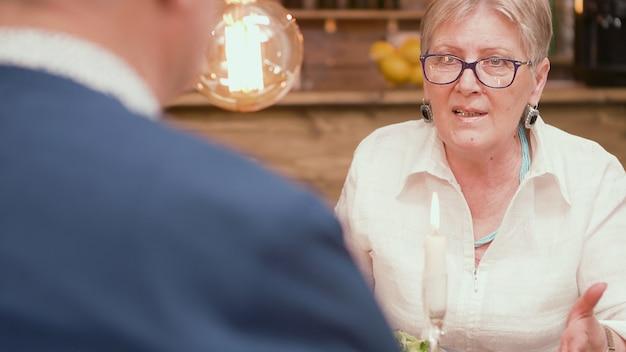 Mulher sênior olhando com amor para o marido durante o jantar em um restaurante. mulher madura. mulher na casa dos sessenta.