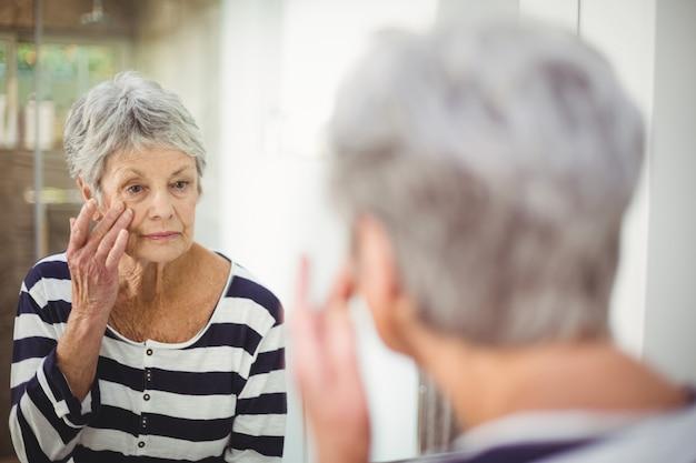 Mulher sênior, olhando para a pele no espelho
