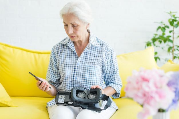 Mulher sênior, olhando para o celular com a câmera virtual