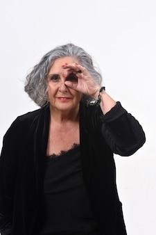 Mulher sênior, olhando por entre os dedos, como se usasse óculos no fundo branco