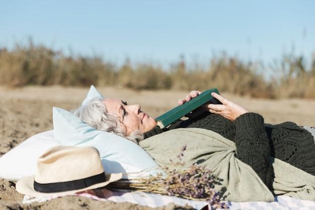 Mulher sênior pacífica que guarda o livro