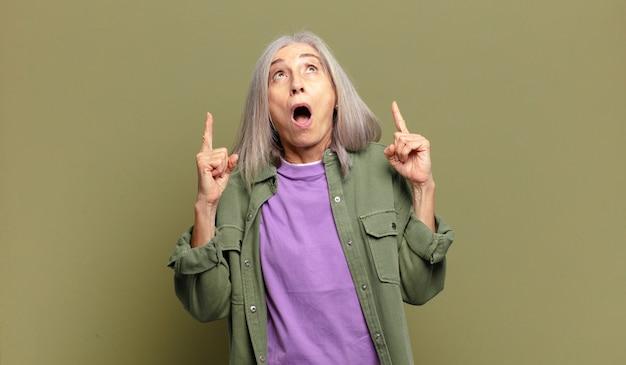 Mulher sênior parecendo chocada, surpresa e boquiaberta, apontando para cima com as duas mãos para copiar o espaço