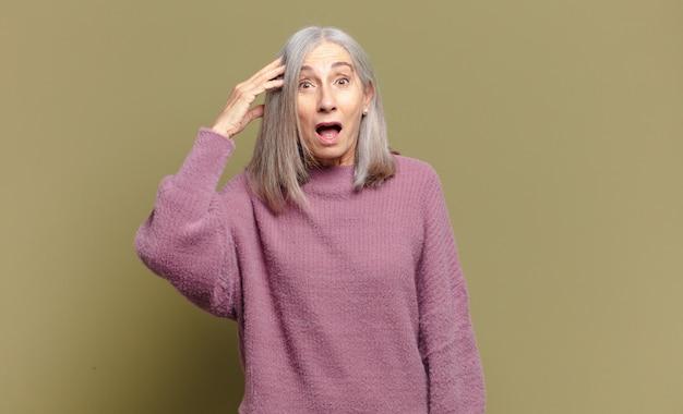 Mulher sênior parecendo feliz, espantada e surpresa, sorrindo e percebendo uma boa notícia incrível
