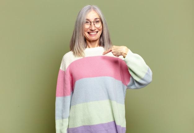 Mulher sênior parecendo feliz, orgulhosa e surpresa, apontando alegremente para si mesma, sentindo-se confiante e elevada