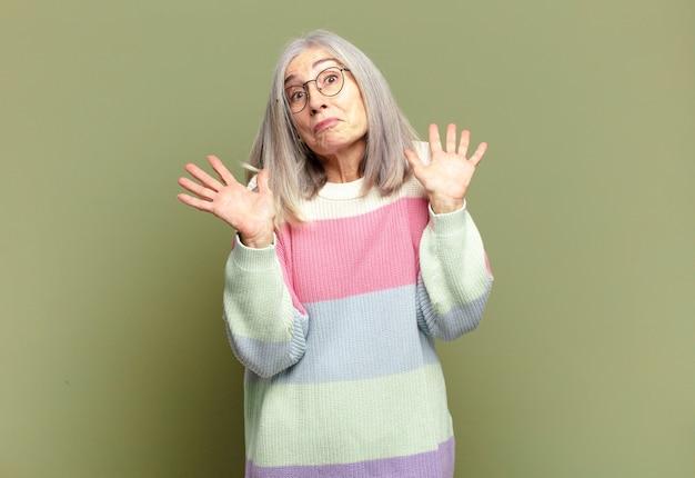 Mulher sênior parecendo nervosa, ansiosa e preocupada, dizendo que não é minha culpa