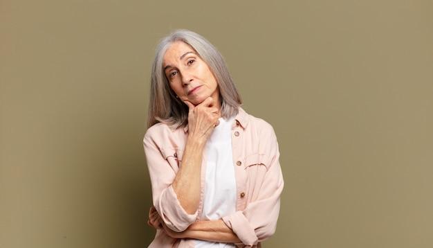 Mulher sênior parecendo séria, confusa, incerta e pensativa, duvidando entre as opções ou escolhas
