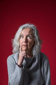 Mulher sênior pensativa com o dedo no queixo, olhando para cima, contra o pano de fundo vermelho