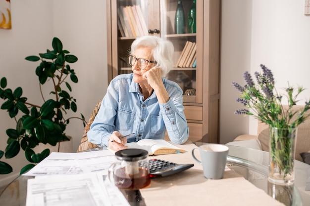 Mulher sênior pensativa contando impostos
