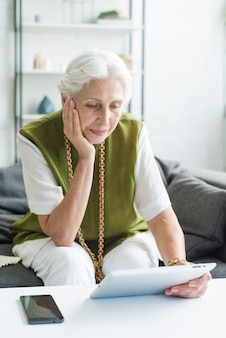 Mulher sênior pensativa olhando para tablet digital