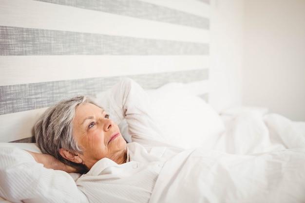 Mulher sênior pensativa relaxante na cama