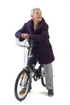 Mulher sênior posando com uma bicicleta no fundo branco