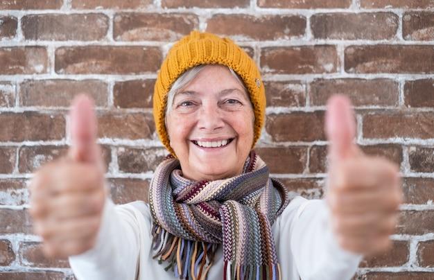 Mulher sênior positiva com polegares para cima sorrindo, olhando para a câmera - fundo da parede de tijolos