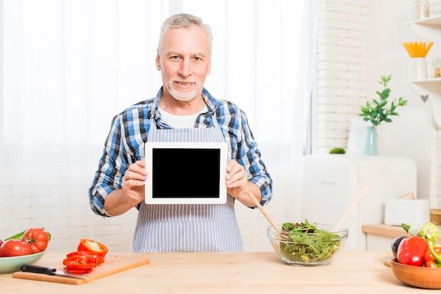 Mulher sênior, preparando a salada de legumes, olhando para o telefone móvel