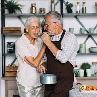 Mulher sênior, provando, alimento, preparado, por, seu, marido, cozinha