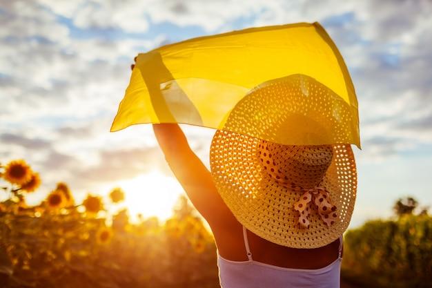 Mulher sênior que anda no campo de florescência do girassol que levanta as mãos com lenço e que tem o divertimento.