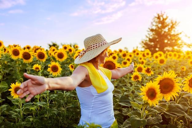 Mulher sênior que anda no campo de florescência do girassol que sente livre e que admira a vista. férias de verão