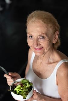 Mulher sênior que come a salada saudável. conceito de estilo de vida de saúde idosos.