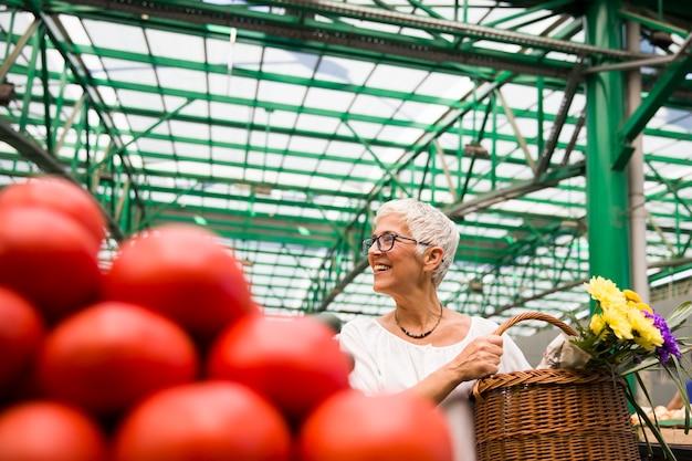 Mulher sênior que compra vegetais orgânicos frescos no mercado
