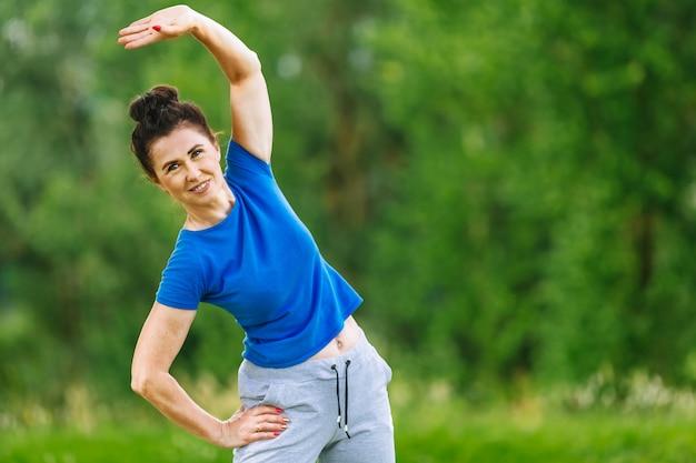 Mulher sênior que exercita no parque.