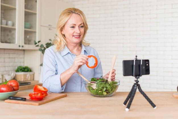 Mulher sênior que faz a chamada de vídeo no celular mostrando a fatia de pimentão ao preparar a salada