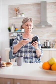 Mulher sênior que paga online usando o aplicativo do telefone e segurando o cartão de crédito na cozinha durante o café da manhã. idoso aposentado que usa o pagamento pela internet, compra do banco doméstico com tecnologia moderna
