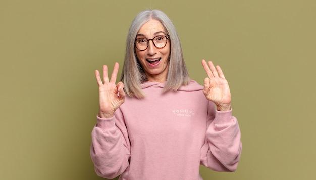 Mulher sênior se sentindo chocada, espantada e surpresa, mostrando aprovação e fazendo um sinal de ok com as duas mãos