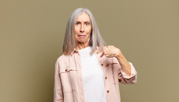 Mulher sênior se sentindo confusa, intrigada e insegura, apontando para si mesma pensando e perguntando quem, eu?