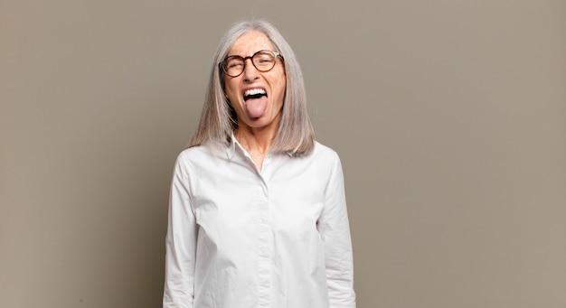 Mulher sênior se sentindo enojada e irritada, mostrando a língua, não gostando de algo nojento e nojento