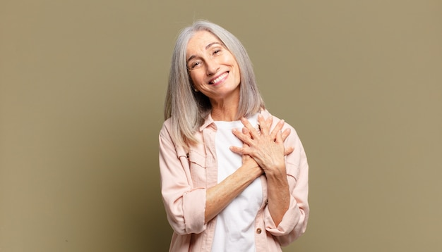 Mulher sênior se sentindo romântica, feliz e apaixonada, sorrindo alegremente e segurando o coração de mãos dadas