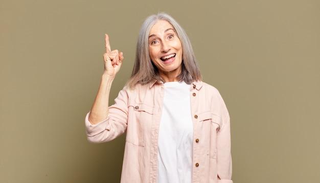 Mulher sênior se sentindo um gênio feliz e animado depois de realizar uma ideia, levantando o dedo alegremente, eureka!